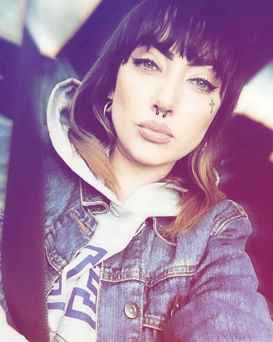 Chica dentro de un auto, tomando una selfie para mostrar su tatuaje en la mejilla
