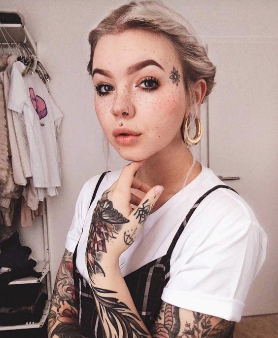 Chica sentada en una silla sosteniendo su rostro con una mano mostrando los tatuajes de su rostro
