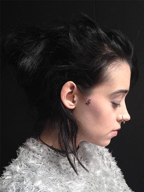 Chica de perfil mostrando su tatuaje en forma de S al lado de su rostro