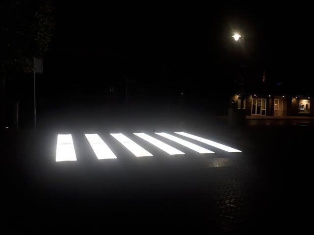 Paso peatonal pintado en blanco e iluminado