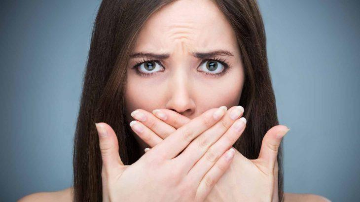 una mujer se cubre la boca con las dos manos