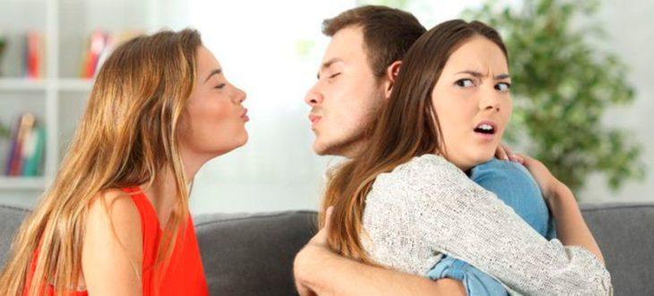 Mujer y hombre infiel abrazados y mujer que le quiere dar un beso al sujeto