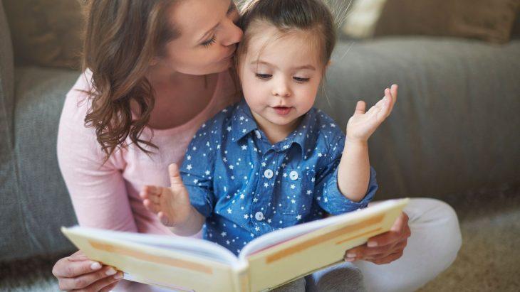 Una mujer besa a su hija en la frente mientras la niña ve un libro que su madre sostiene