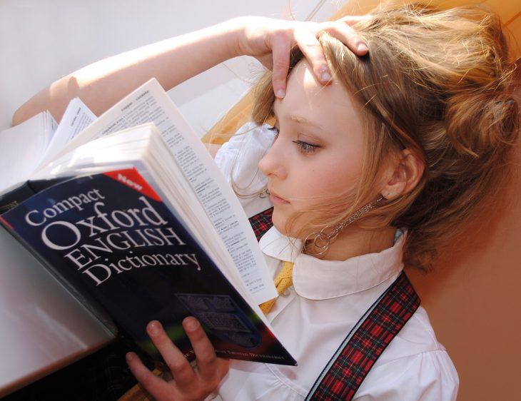 Una niña con un arete largo, blusa blanca y pechera de colegiala lee un diccionario Oxford