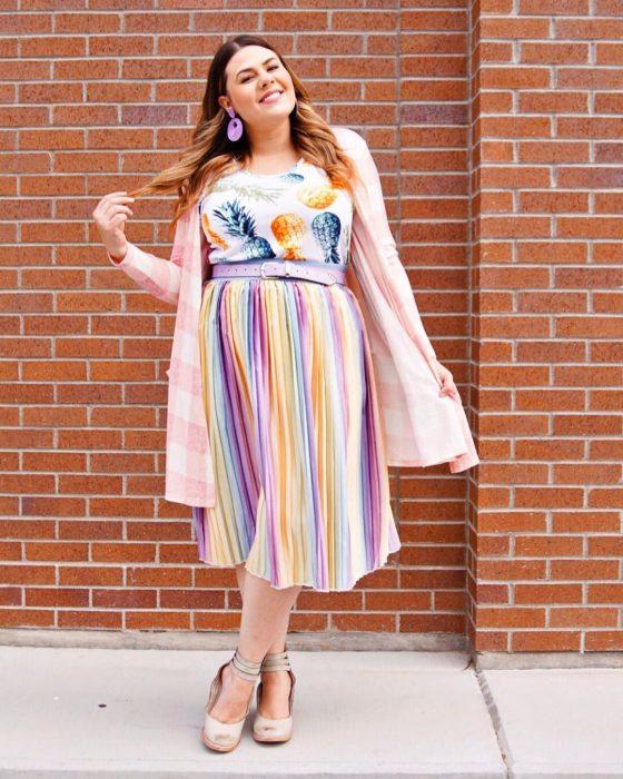 Atuendos para chicas plus size; chica con falda tableada de colores y blusa con estampado de piñas