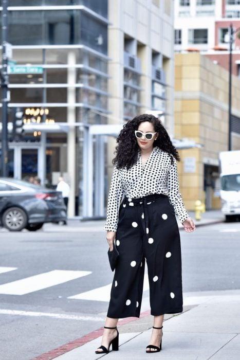 Atuendos para chicas plus size; chica de cabello chino con pantalón y blusa polka dots