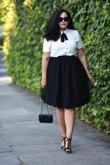 Atuendos para chicas plus size; chica de cabello chino con blusa blanca y falda a las rodillas negra