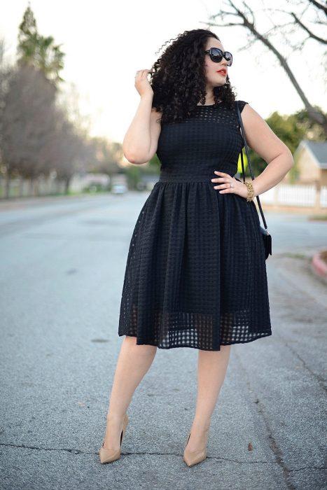Atuendos para chicas plus size; chica de cabello chino con vestido negro abajo de las rodillas, sin manga y de encaje