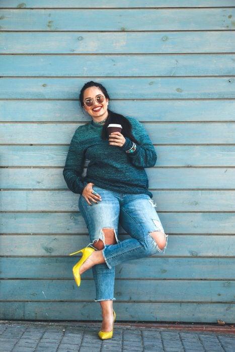 Atuendos para chicas plus size; chica sonriendo con suéter verde, jean y zapatillas amarillas