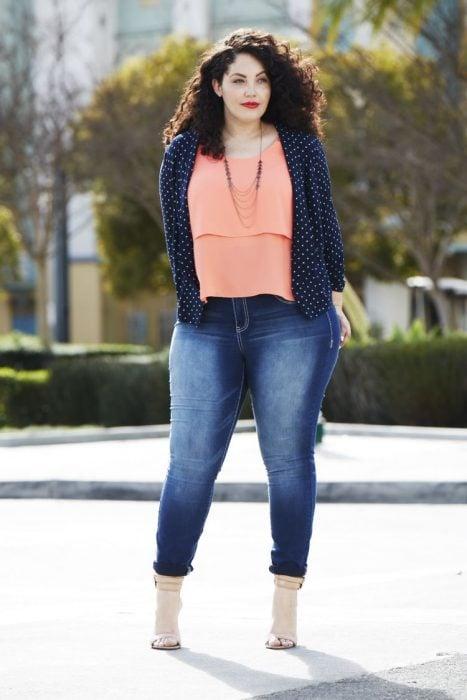 Atuendos para chicas plus size; chica de cabello chino con pantalón de mezclilla