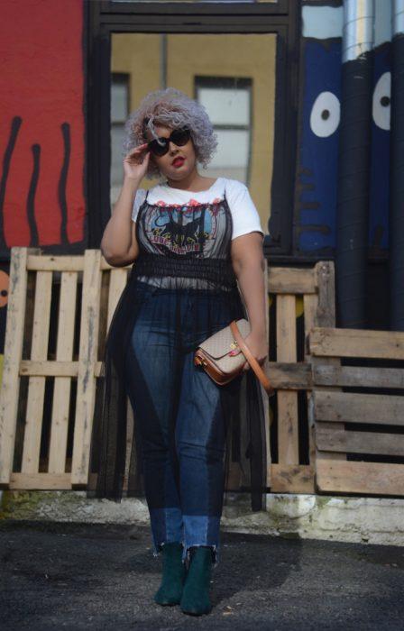 Atuendos para chicas plus size; chica de cabello corto, chino y de color lila, con vestido tranpsarente arriba de blusa básica y jean