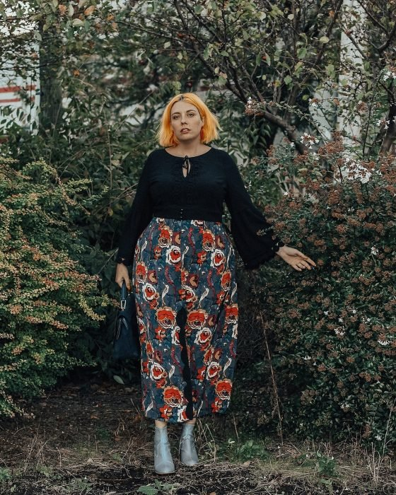 Atuendos para chicas plus size; chica de cabello corto y anaranjado, con pantalón floreado en el jardín