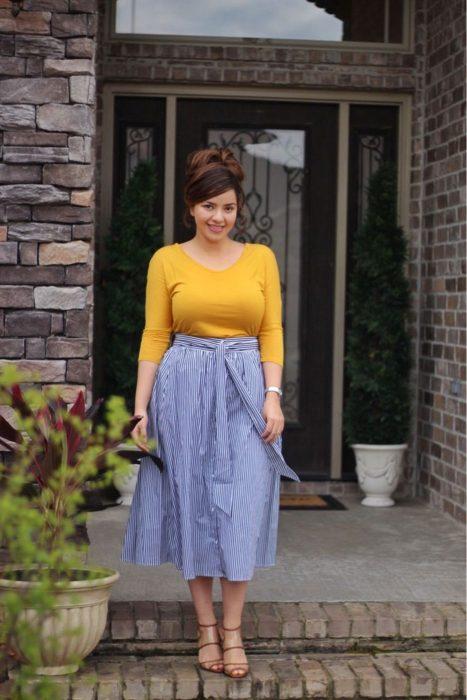 Atuendos para chicas plus size; chica con chongo alto, blusa amarilla y falda rayada