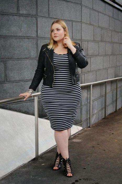 Atuendos para chicas plus size; mujer rubia con vestido de rayas negras y blancas horizontales y chamarra de cuero negro
