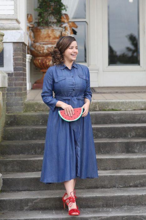 Atuendos para chicas plus size; chica con vestido denim y bolsa de mano en forma de sandía