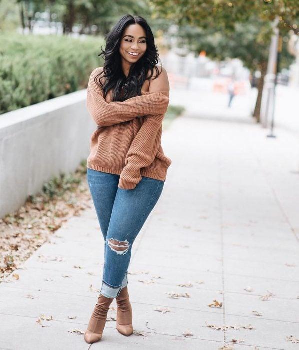 Atuendos para chicas plus size; chica morena con pantalón de mezclilla desgastado y suéter oversized