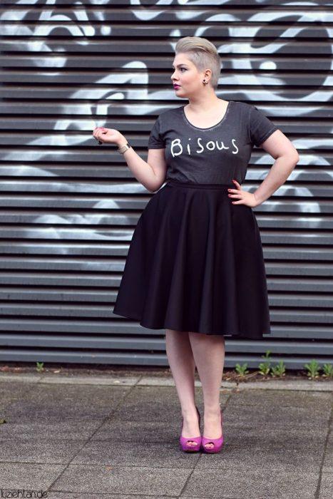 Atuendos para chicas plus size; chcia rubia de cabello corto con falda negra y zapatillas rosas