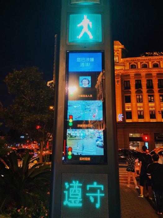 un semáforo chino en que se exhibe a alguien que cruzó indebidamente