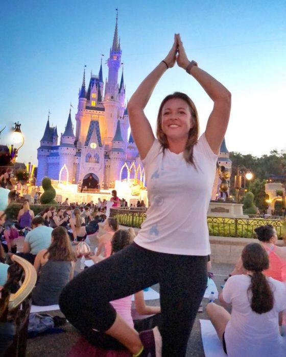 Mujer haciendo una pose de Yoga mientras que está sucediendo el atardecer