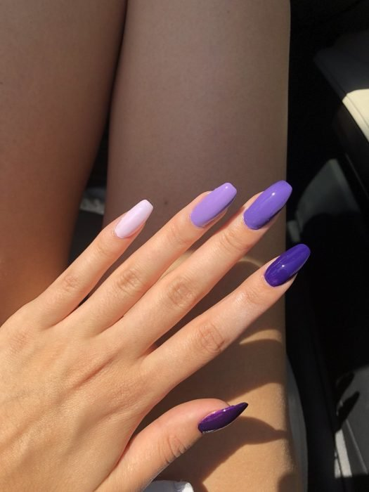 Manicura; uñas largas de diferentes tonalidades de morado, degradado