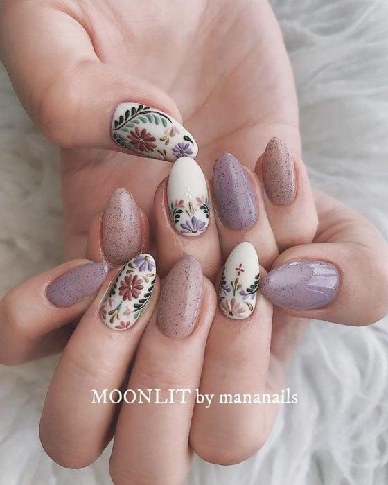 Manicura; uñas de almendra con flores y textura de roca