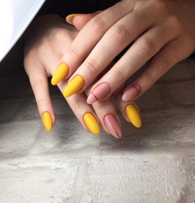Manicura; uñas de almendra color amarillo canario y rosa palo con líneas horizontales y verticales