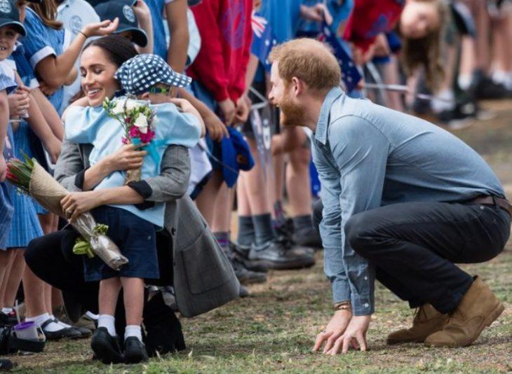 Meghan Markle abraza a un niño mientras Harry a su lado en cuclillas le hace cariños