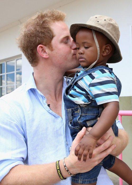 Príncipe Harry con un niño africano en los brazos a quien besa en la mejilla