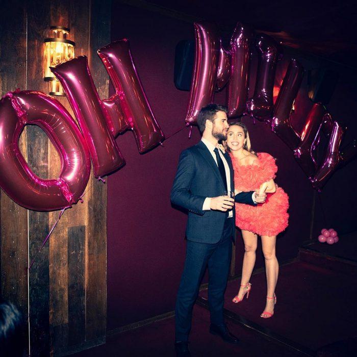 Miley Cyrus y Liam Hemsworth en el cumpleaños de la cantante, globos rosas en la pared