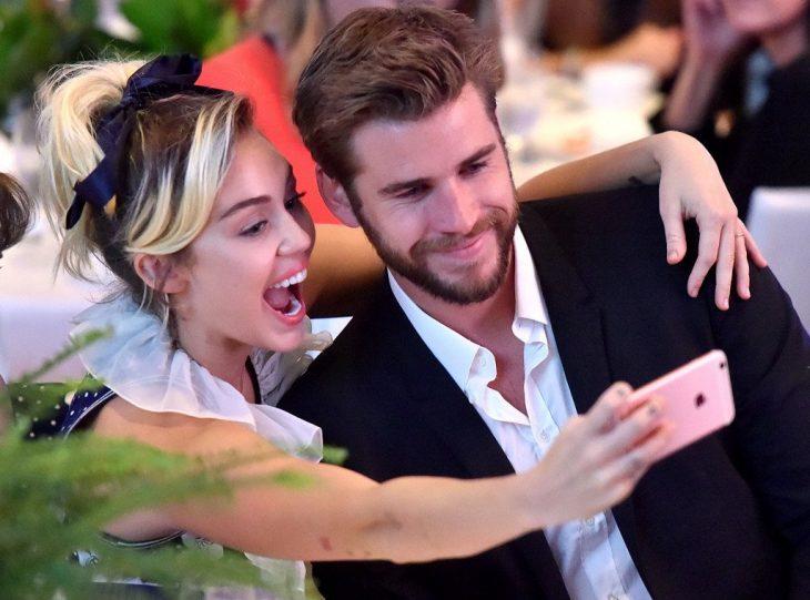 Miley Cyrus tomándose una foto con Liam Hemsworth