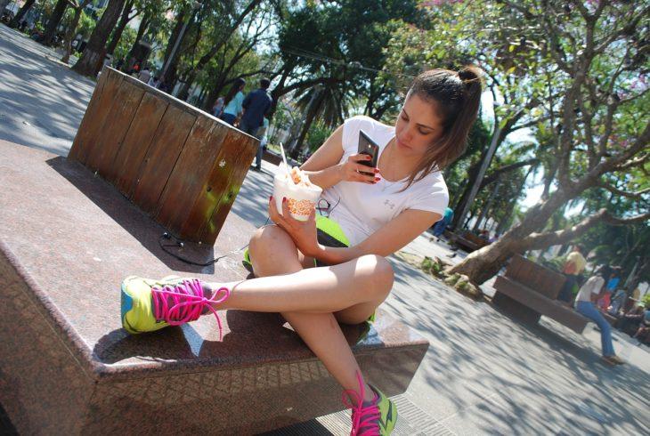 una mujer con ropa deportiva sentada en un banco en un parque revisando su celular