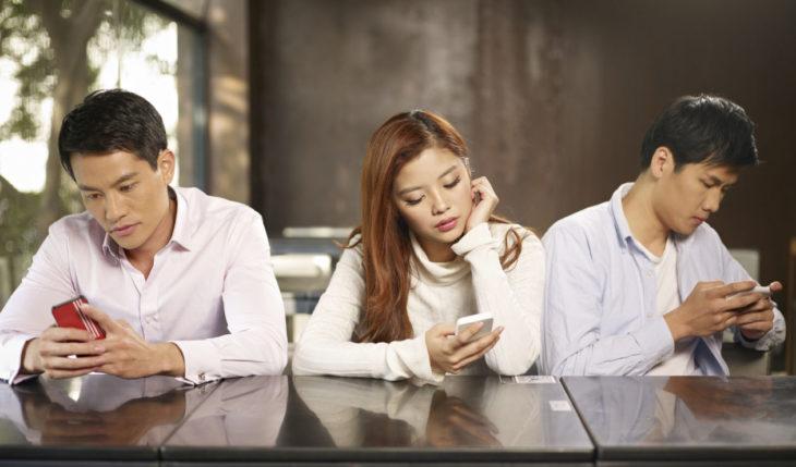 dos hombres y una mujer con rasgos asiáticos en una misma mesa revisando cada uno sus celulares