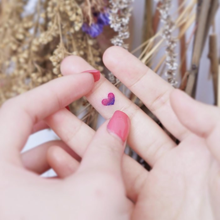 Chinese tattoo artist, Mini Lau; Small, feminine tattoo with pastel heart colors on the middle finger