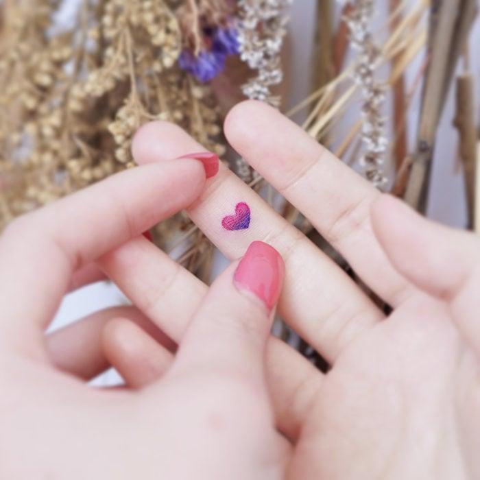 Tatuadora china, Mini Lau; tatuaje pequeño y femenino con colores pastel de corazón en el dedo medio
