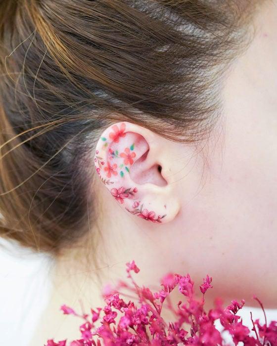 Tatuadora china, Mini Lau; tatuaje pequeño y femenino con colores pastel de flores rojas y anaranjadas en la oreja