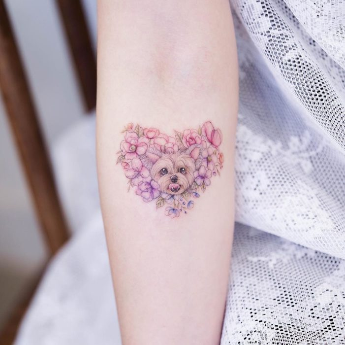 Chinese tattoo artist, Mini Lau; Small and feminine tattoo with pastel colors yorkie dog in a heart of flowers