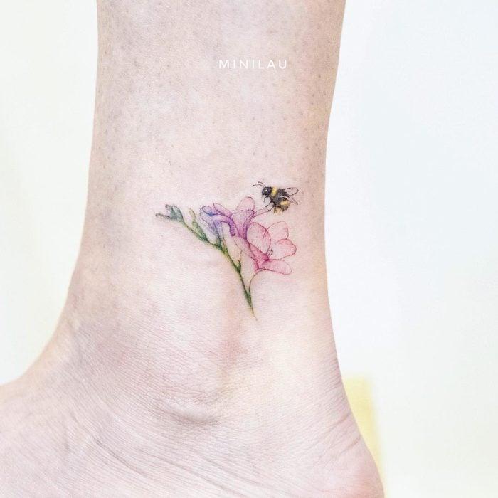 Tatuadora china, Mini Lau; tatuaje pequeño y femenino con colores pastel de abeja en una flor rosa en el tobillo