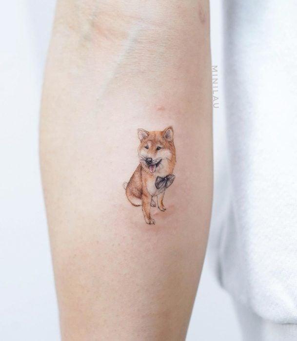 Tatuadora china, Mini Lau; tatuaje pequeño y femenino con colores pastel de perro shiba con moño