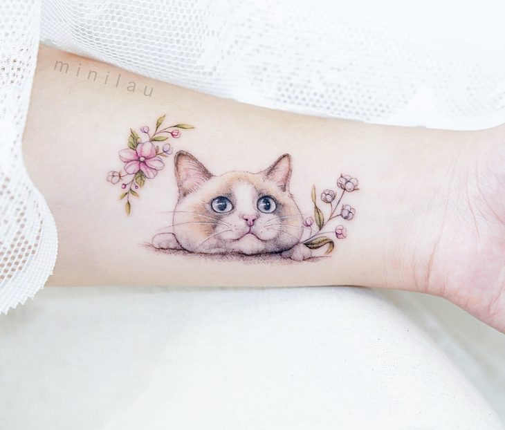 Tatuadora china, Mini Lau; tatuaje pequeño y femenino con colores pastel de gato siamés con flores rosas y lilas