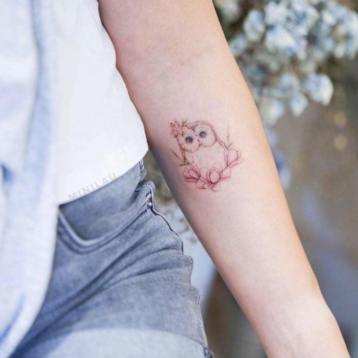 Tatuadora china, Mini Lau; tatuaje pequeño y femenino con colores pastel de búho bebé con flores rosas