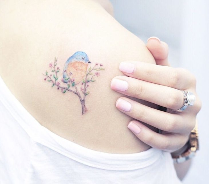 Chinese tattoo artist, Mini Lau; Small and feminine tattoo with pastel colors of blue bird on a branch with pink flowers