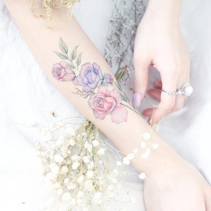 Chinese tattoo artist, Mini Lau; Small, feminine tattoo with pastel rose colors on the arm