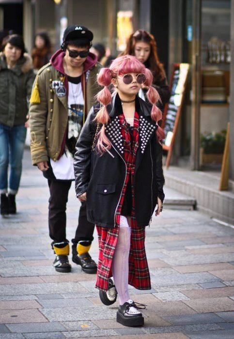 Moda japonesa harajuku; niña de cabello rosa con peinado de trenzas, con vestido de estampado esconcés y chamarra de piel oversized con estoperoles y zapatos de plataforma