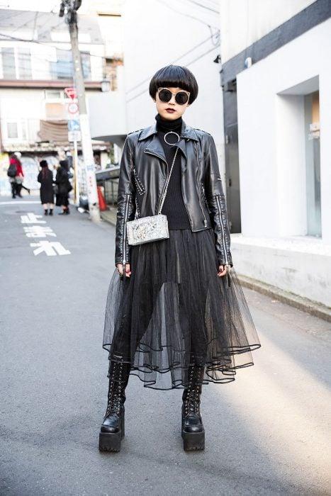Moda japonesa harajuku; chica gótica con corte pixie, lentes redondos y grandes, chamarra de cuero con remaches, falda de tul y botas largas de plataforma