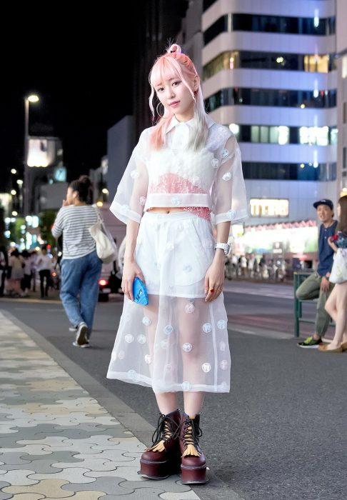 Moda japonesa harajuku; mujer con cabello rosa con ropa de encaje blanco y botas color vino de plataforma