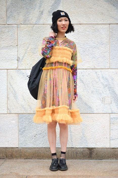 Moda japonesa harajuku; chica con vestido floreado debajo de vestido transparente anaranjado, con gorra y mochila