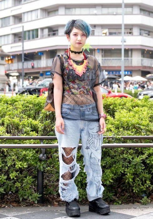 Moda japonesa harajuku; chica de cabello corto color azul, con pantalones holgados y desgastados, zapatos de plataforma y medias de red