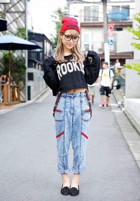 Moda japonesa harajuku; chica con lentes de aumento grandes, gorra y pantalón holgado con tirantes