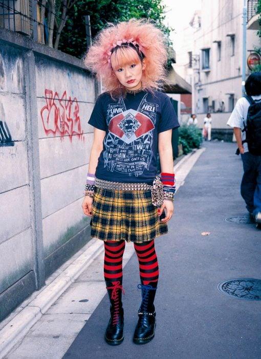 Moda japonesa harajuku; chica con estilo punk de cabello esponjado y rosa, falda de estampado de cuadros y medias de rayas rojas
