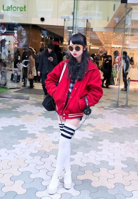 Moda japonesa harajuku; chica de cabello negro y largo, con lentes redondos, chaqueta de equipo de fútbol, zapatos de plataforma y calcetas largas